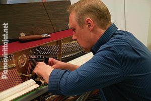 Matti Rassi työssään pianoa virittämässä